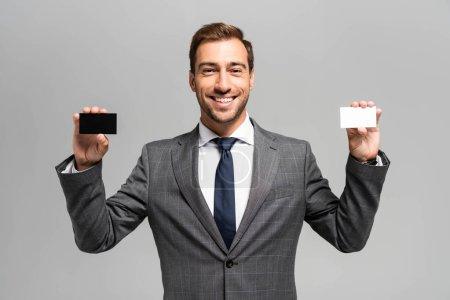 Photo pour Bel homme d'affaires souriant en costume tenant des cartes d'affaires isolées sur gris - image libre de droit
