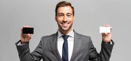 Foto de Foto panorámica de un empresario guapo y sonriente con tarjetas de visita aisladas en gris. - Imagen libre de derechos
