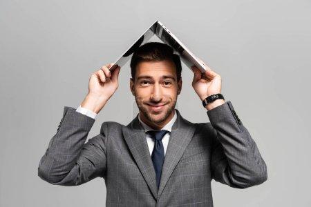 Photo pour Homme d'affaires beau et souriant en costume tenant ordinateur portable au-dessus de la tête isolé sur gris - image libre de droit