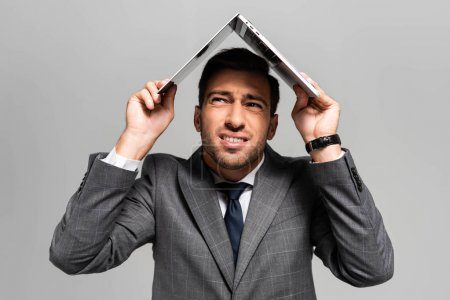 handsome and frightened businessman in suit holding laptop above head isolated on grey