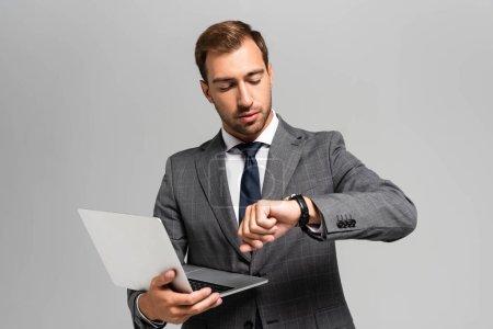 Foto de Guapo hombre de negocios en traje portador de portátil y mirando a reloj de pulsera aislado en gris. - Imagen libre de derechos