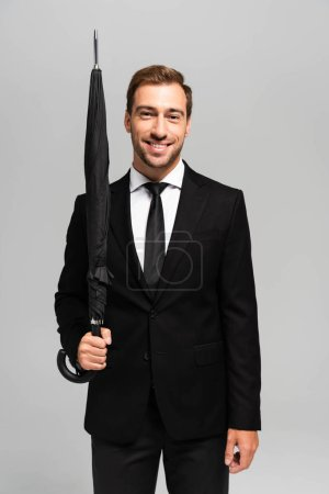 Photo for Handsome and smiling businessman in suit holding umbrella isolated on grey - Royalty Free Image