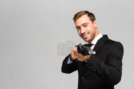 Photo pour Foyer sélectif de beau et souriant homme d'affaires en costume tenant parapluie isolé sur gris - image libre de droit
