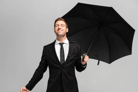 handsome and smiling businessman with closed eyes in suit holding umbrella isolated on grey