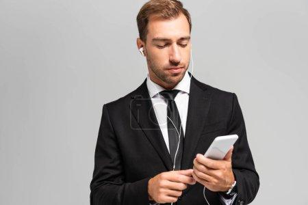 Photo pour Bel homme d'affaires en costume avec écouteurs utilisant un smartphone isolé sur gris - image libre de droit