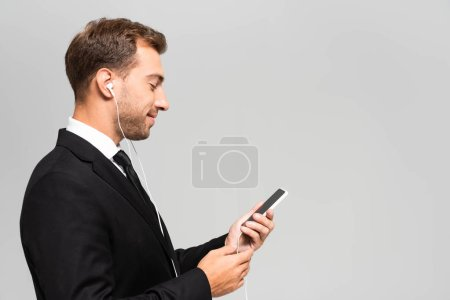 side view of handsome and smiling businessman in suit with earphones using smartphone isolated on grey