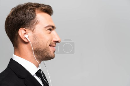 Photo pour Side view of beautiful and smiling business man in suit listening music with earphones isolated on grey - image libre de droit