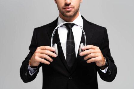 Photo pour Vue recadrée de l'homme d'affaires en costume tenant des écouteurs isolés sur gris - image libre de droit