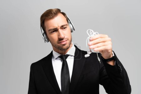 Photo for Sad businessman in suit with headphones listening music and looking at earphones isolated on grey - Royalty Free Image