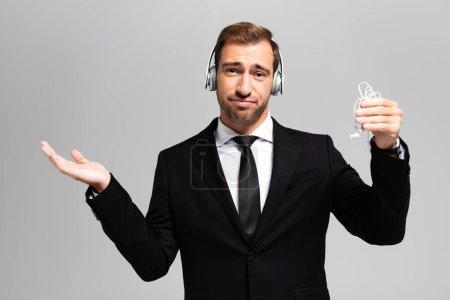 Photo pour Homme d'affaires triste en costume avec écouteurs écouter de la musique et tenir les écouteurs isolés sur gris - image libre de droit