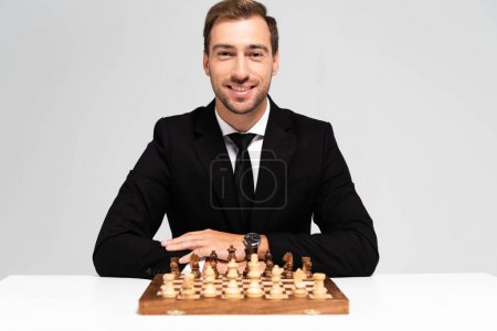 Photo pour Homme d'affaires souriant et beau en costume assis près de l'échiquier isolé sur gris - image libre de droit