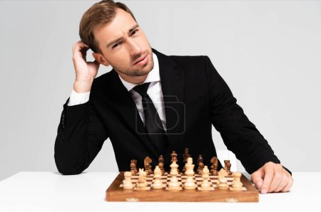 Photo for Pensive and handsome businessman in suit sitting near chessboard isolated on grey - Royalty Free Image