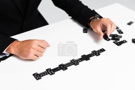 Photo for Cropped view of businessman in suit playing domino - Royalty Free Image