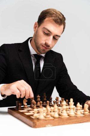 Photo pour Bel homme d'affaires en costume jouant aux échecs isolé sur gris - image libre de droit