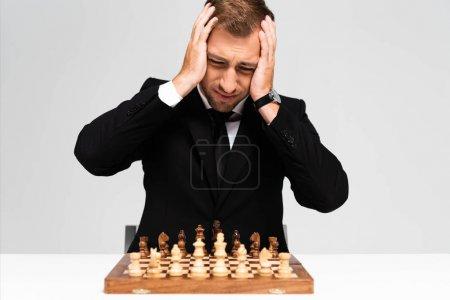 Foto de Triste y hermoso hombre de negocios en traje mirando al tablero de ajedrez aislado en gris. - Imagen libre de derechos