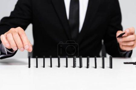 Photo pour Vue recadrée de l'homme d'affaires en costume cueillant domino de rangée isolé sur gris - image libre de droit