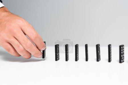 Foto de Vista recortada del hombre que toma el dominó de la fila aislada en gris - Imagen libre de derechos