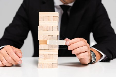 Photo for Cropped view of businessman in suit playing blocks wood game isolated on grey - Royalty Free Image
