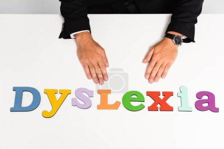 Photo pour Vue recadrée de l'homme d'affaires en costume assis près de lettrage dyslexie - image libre de droit