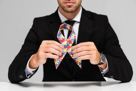 cropped view of businessman in suit holding symbol of autism isolated on grey