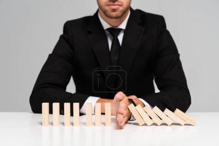 Photo pour Crochet vue de l'homme d'affaires en costume pour empêcher les blocs de bois de tomber isolés sur le gris - image libre de droit