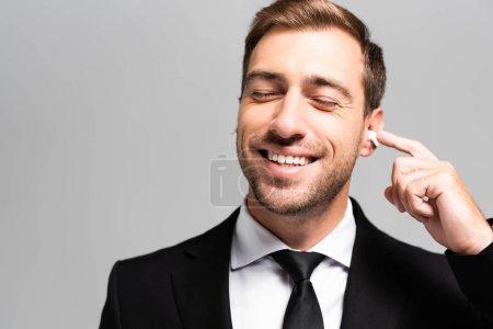 Photo pour Homme d'affaires beau et souriant en costume écoutant de la musique isolée sur gris - image libre de droit