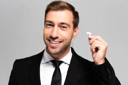 Photo pour Homme d'affaires beau et souriant en costume tenant des écouteurs isolés sur gris - image libre de droit