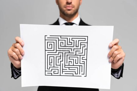 cropped view of businessman holding paper with labyrinth isolated on grey