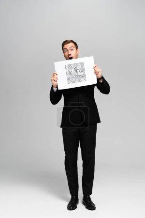 Photo pour Bel homme d'affaires choqué en costume tenant du papier avec un labyrinthe sur fond gris - image libre de droit