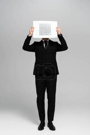 Photo for Businessman obscuring face with paper with labyrinth on grey background - Royalty Free Image