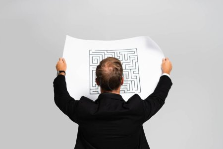 Photo pour Back view of business man in suit looking at paper with labyrinth isolated on grey - image libre de droit