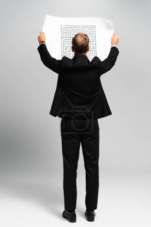 Foto de Back view of business in suit looking at paper with labyrinth on grey background. - Imagen libre de derechos