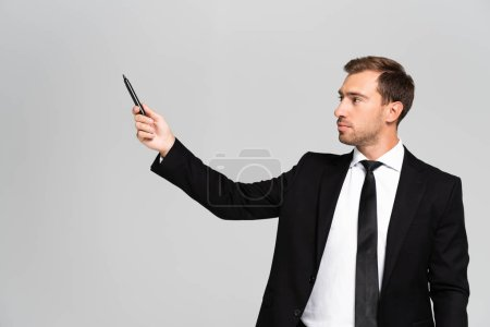 Photo for Handsome businessman businessman in suit holding marker isolated on grey - Royalty Free Image