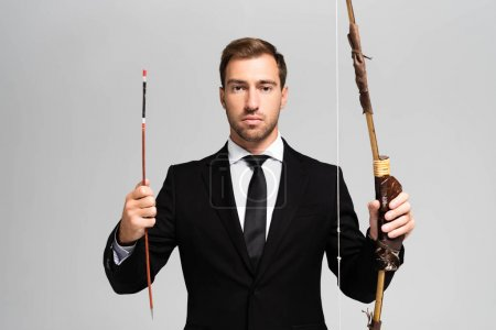 Photo for Handsome businessman in suit holding bow and arrow isolated on grey - Royalty Free Image