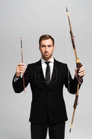 Photo pour Bel homme d'affaires en costume tenant un arc et une flèche isolés sur gris - image libre de droit