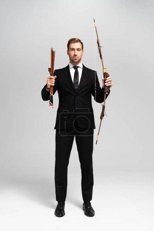 Foto de Guapo hombre de negocios en traje sosteniendo arco y flechas sobre fondo gris. - Imagen libre de derechos