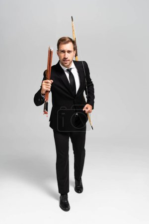 Photo for Handsome businessman in suit holding bow, arrows and walking on grey background - Royalty Free Image