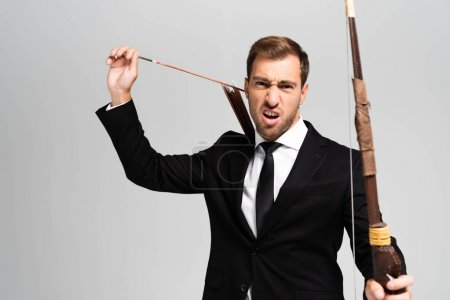 Photo for Angry businessman in suit holding bow and arrow isolated on grey - Royalty Free Image