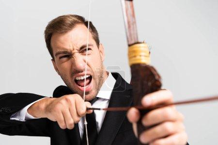 Foto de Enfoque selectivo del hombre de negocios enfadado en traje sujetando arco y disparando con flecha aislada sobre gris. - Imagen libre de derechos