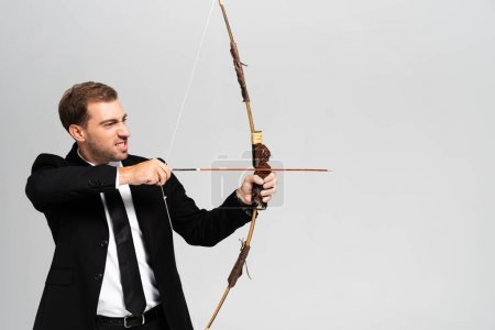 Photo for Angry businessman in suit holding bow and shooting with arrow isolated on grey - Royalty Free Image