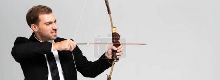 Photo pour Photo panoramique d'un homme d'affaires en colère en costume tenant un arc et tirant avec une flèche isolée sur gris - image libre de droit