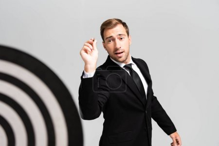 Photo for Selective focus of businessman in suit playing darts isolated on grey - Royalty Free Image