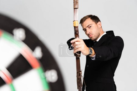 Photo for Selective focus of handsome businessman in suit holding bow and shooting at target isolated on grey - Royalty Free Image