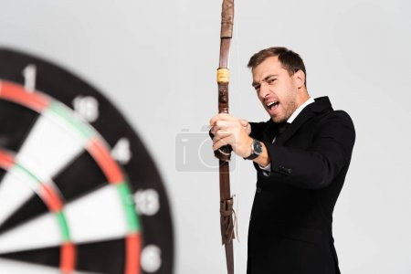Photo for Selective focus of angry businessman in suit holding bow and shooting at target isolated on grey - Royalty Free Image