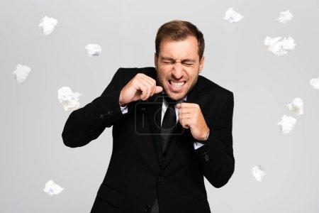 Photo pour Beau et effrayé homme d'affaires en costume debout près de tomber froissé papiers isolés sur gris - image libre de droit