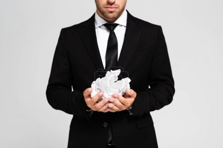 cropped view of businessman in suit holding crumpled papers isolated on grey