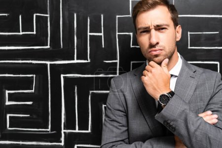 Photo for Handsome and pensive businessman in suit standing near labyrinth - Royalty Free Image
