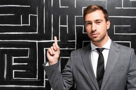 Foto de Un empresario guapo en traje de pie cerca del laberinto y mostrando el signo de la idea. - Imagen libre de derechos