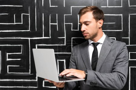 handsome businessman in suit standing near labyrinth and using laptop