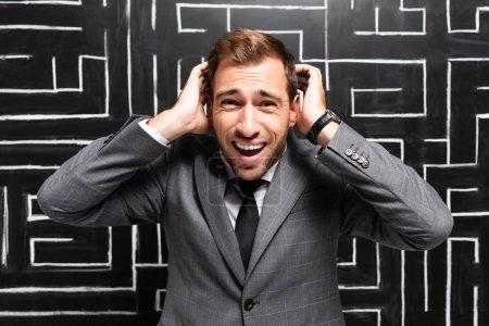 Photo pour Homme d'affaires en colère en costume debout près du labyrinthe et touchant la tête - image libre de droit